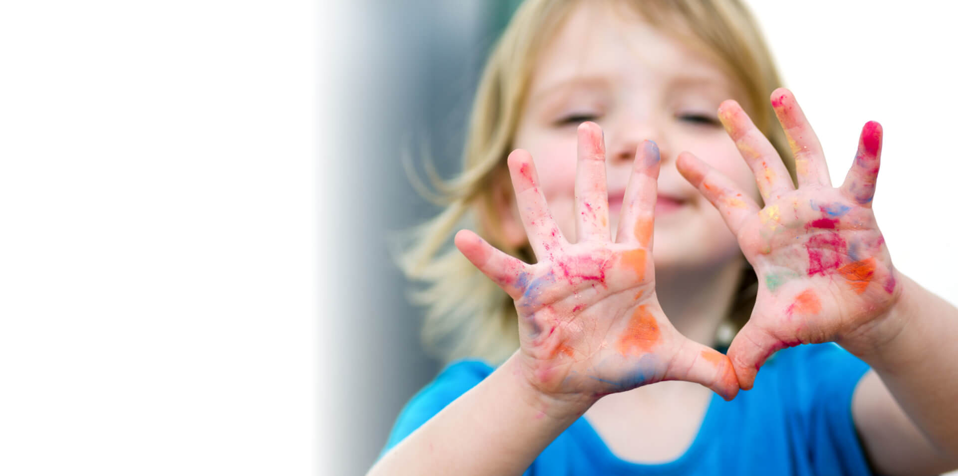 Cute preschooler girl with smile showing colored hands