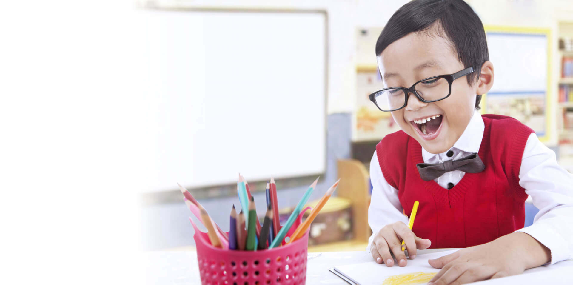 Happy student boy drawing with pencil colors